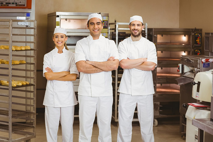 Team of bakers smiling at camera in a commercial kitchen